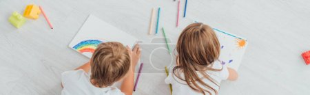 Photo for Top view of brother and sister in pajamas lying on floor and drawing with felt pens in sketchbooks, panoramic shot - Royalty Free Image