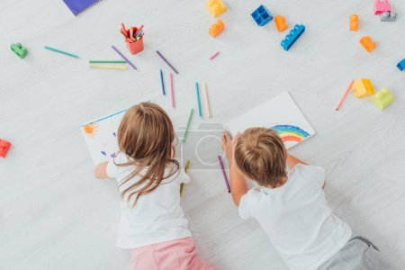 Photo for Top view of brother and sister in pajamas lying on floor near building blocks and drawing with felt pens in sketchbooks - Royalty Free Image