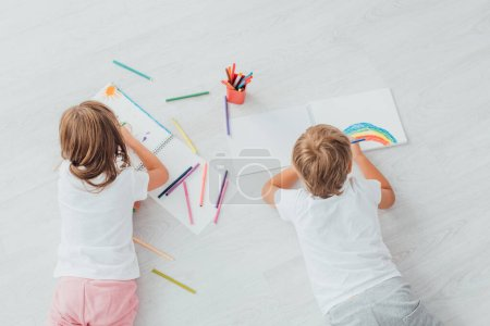 Photo for Top view of brother and sister in pajamas lying on floor and drawing with felt pens in sketchbooks - Royalty Free Image