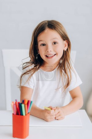 Photo for Selective focus of excited girl in white t-shirt holding felt pen and looking at camera - Royalty Free Image