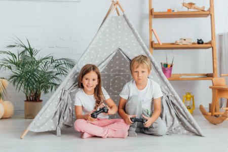 Photo for KYIV, UKRAINE - JULY 21, 2020: brother and sister in pajamas sitting on floor near play tent and playing video game - Royalty Free Image