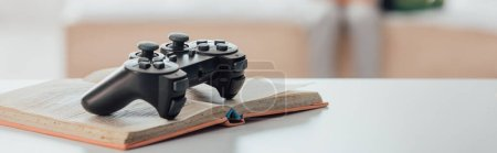 Photo for Website header of black joystick over open book on white table - Royalty Free Image