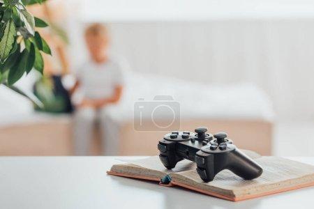 KYIV, UCRANIA - 21 de julio de 2020: enfoque selectivo del joystick en el libro abierto y silueta del niño sentado en la cama cerca de la mochila escolar