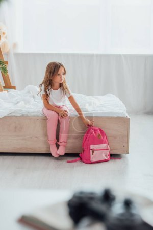 selective focus of girl in pajamas touching school backpack while sitting on floor in pajamas