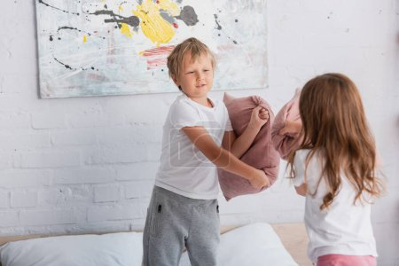 Photo pour Frères et sœurs en pyjama s'amuser tout en se battant avec un oreiller dans les chambres - image libre de droit