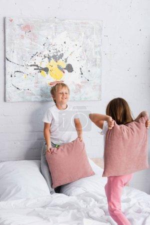 Photo pour Frère et soeur en pyjama s'amuser tout en se battant avec des oreillers dans les chambres - image libre de droit