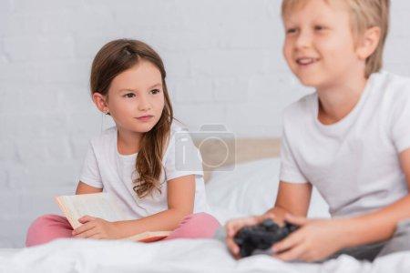 Photo pour KYIV, UKRAINE - 21 juillet 2020 : mise au point sélective de la fille avec un livre regardant frère excité jouer à un jeu vidéo dans la chambre à coucher - image libre de droit