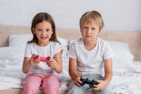 KYIV, UKRAINE - JULY 21, 2020: excited girl and concentrated brother in pajamas playing video game in bedroom
