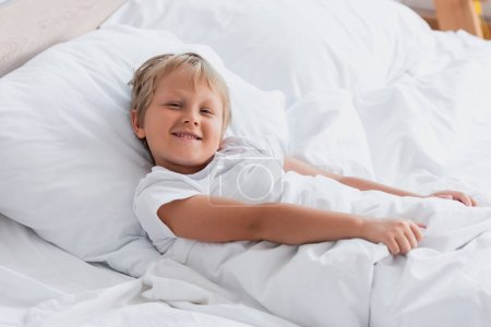 Photo pour Garçon éveillé regardant la caméra tout en étant couché dans le lit - image libre de droit
