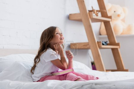 dreamy girl in pajamas looking up while sitting on bed with book