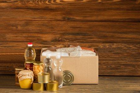 boîte en carton avec gruaux près de l'eau, huile, aliments en conserve et miel sur fond en bois, concept de charité