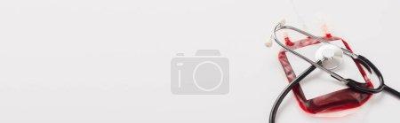 Photo pour Paquet de don de sang avec étiquette vierge et stéthoscope sur blanc, plan panoramique - image libre de droit