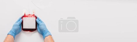 Photo for Cropped view of doctor holding blood donation package with blank label on white background, panoramic shot - Royalty Free Image