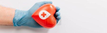 Foto de Vista recortada de la mano masculina en guante de látex con corazón rojo en blanco, concepto de donación de sangre - Imagen libre de derechos