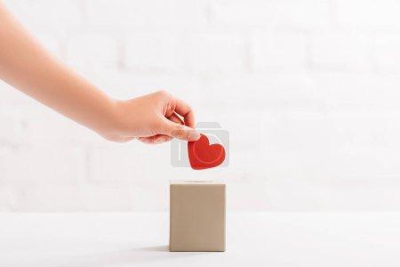 Ausgeschnittene Ansicht einer weiblichen Hand, die rotes Herz in Schachtel auf weißem Hintergrund legt, Spendenkonzept