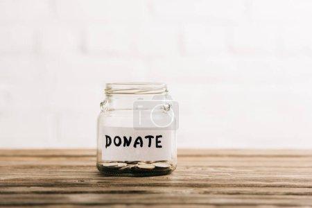 Penny-Glas mit Spendenaufdruck auf hölzerner Oberfläche auf weißem Hintergrund