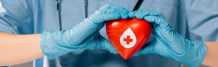 Photo for Cropped view of doctor with stereoscope holding red heart, blood donation concept - Royalty Free Image