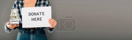 Photo pour Vue recadrée de femme tenant la carte avec faire un don ici lettrage et pot avec de l'argent sur fond gris, vue panoramique - image libre de droit