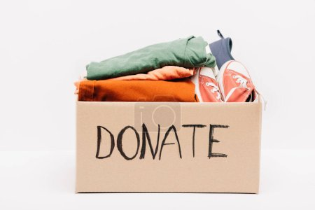Photo for Cardboard box with donated clothes and footwear isolated on white, charity concept - Royalty Free Image