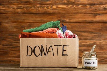 Photo pour Argent dans un bocal près de la boîte en carton avec des dons de lettres et de vêtements sur fond en bois, concept de charité - image libre de droit