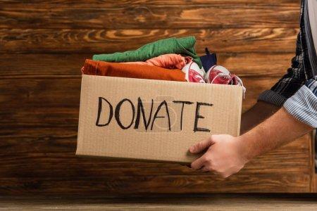 Photo pour Vue recadrée de l'homme tenant boîte en carton avec des dons de lettres et de vêtements sur fond en bois, concept de charité - image libre de droit