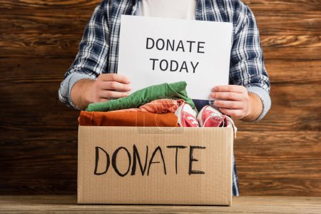 Photo pour Vue recadrée de l'homme tenant faire un don aujourd'hui carte près boîte en carton avec des vêtements sur fond en bois, concept de charité - image libre de droit