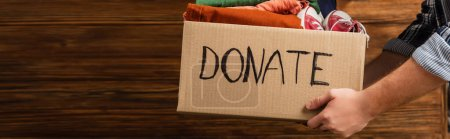 Photo for Cropped view of man holding cardboard box with donate lettering and clothes on wooden background, charity concept - Royalty Free Image