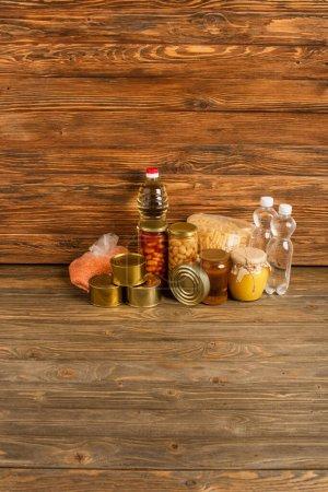 gruaux près de l'eau, huile, aliments en conserve et miel sur fond en bois, concept de charité