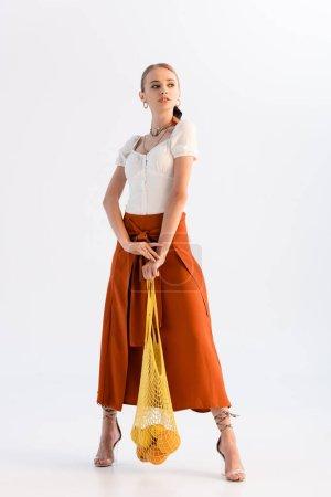 volle Länge Ansicht der modischen Frau posiert mit Zitrusfrüchten in String-Tasche isoliert auf weiß