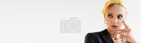 fashionable woman in yellow headscarf and golden accessories posing isolated on white, panoramic shot