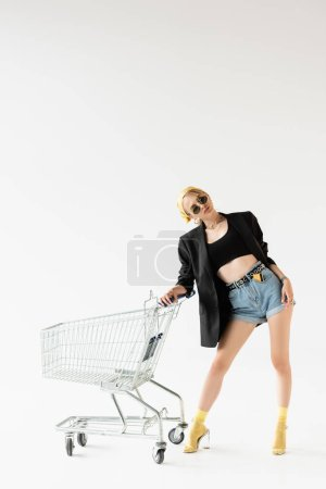 Photo for Fashionable woman in black and yellow outfit with credit card in shorts posing near shopping cart isolated on white - Royalty Free Image