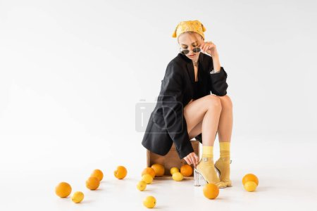 fashionable woman posing on wooden box near scattered citrus fruits on white background