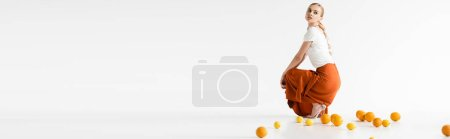 Photo for Side view of elegant blonde woman posing near citrus fruits on white background, panoramic shot - Royalty Free Image