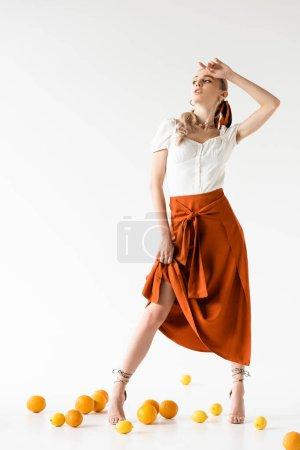 Photo for Elegant blonde woman posing near citrus fruits on floor on white background - Royalty Free Image
