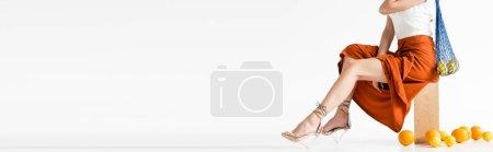 Photo pour Vue recadrée de femme élégante posant avec un sac à ficelle près d'agrumes éparpillés sur fond blanc, vue panoramique - image libre de droit
