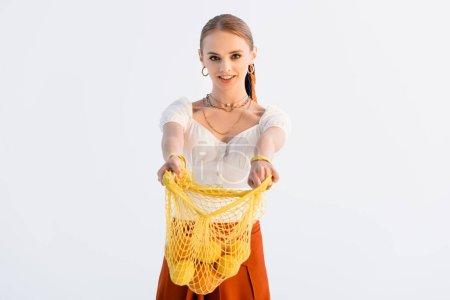 elegante blonde Frau gibt String-Tasche mit Zitrusfrüchten isoliert auf weiß