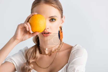 Photo pour Élégante femme blonde au visage obscur posant à l'orange isolé sur blanc - image libre de droit