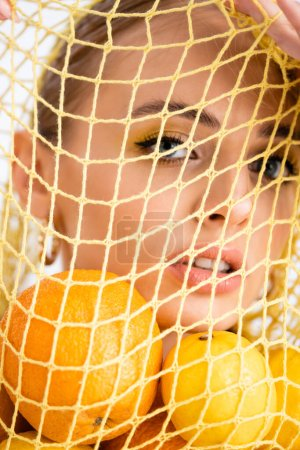 portrait of woman in string bag with citrus fruits
