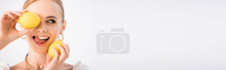 Photo for Funny blonde woman holding lemons and showing tongue isolated on white, panoramic shot - Royalty Free Image