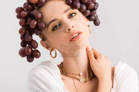Photo pour Portrait de femme blonde rustique posant avec des raisins sur la tête isolé sur blanc - image libre de droit