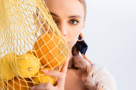 rustic blonde woman posing with citrus fruits in yellow string bag in front of face isolated on white
