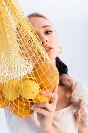 Photo pour Femme blonde rustique posant avec des agrumes dans un sac à ficelle jaune isolé sur blanc - image libre de droit