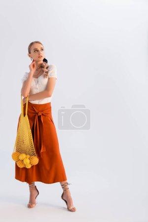 verträumte rustikale blonde Frau posiert mit Zitrusfrüchten in gelbem Stringbeutel isoliert auf weißem Grund