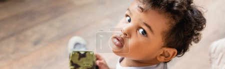 Photo for Horizontal image of african american boy looking at camera while holding toy, overhead view - Royalty Free Image