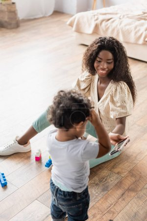 high angle view of african american woman sitting on floor and showing smartphone to little son