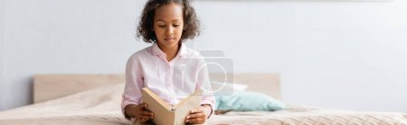 horizontal image of focused african american girl in white shirt reading book while sitting in bedroom