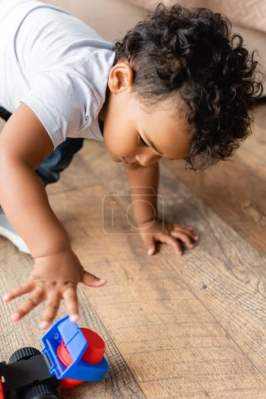 selective focus of curly african american kid playing with toy truck on wooden floor at home
