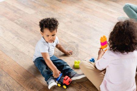 Photo pour Vue grand angle des enfants afro-américains jouant avec des blocs de construction et camion jouet sur le sol à la maison - image libre de droit