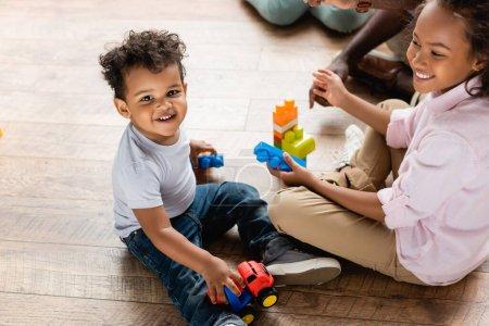 Photo pour Vue grand angle de frère afro-américain et soeur jouer avec camion jouet et blocs de construction sur le sol à la maison - image libre de droit
