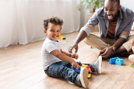 Photo pour Excité homme afro-américain près de fils jouer avec camion jouet sur le sol en bois - image libre de droit